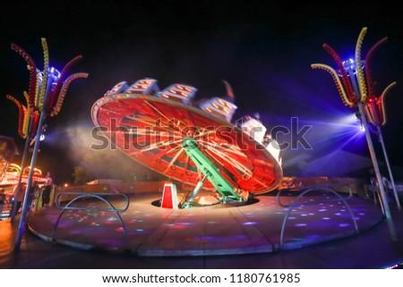 An illuminated rotating circular device in an amusement park. #1180761985