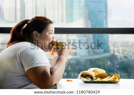Picture of fat woman eating a hamburger in the restaurant while sitting by the window