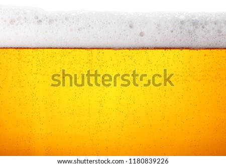 Close up background texture of lager beer with bubbles and froth in glass, low angle side view #1180839226