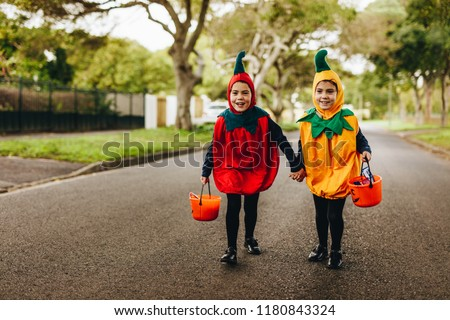 Two little girls in halloween costume trick or treating on the road. Two identical twin sisters in halloween costume walking outdoors with halloween bucket. #1180843324