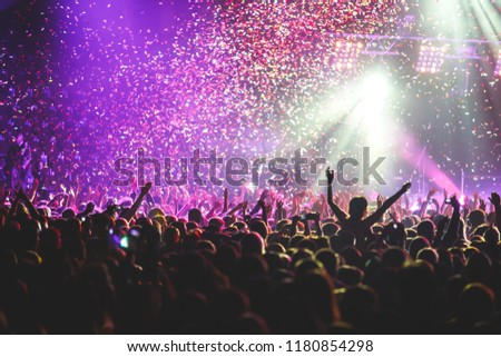 A crowded concert hall with scene stage lights, rock show performance, with people silhouette  #1180854298
