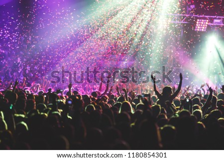 A crowded concert hall with scene stage lights, rock show performance, with people silhouette  #1180854301