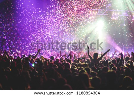 A crowded concert hall with scene stage lights, rock show performance, with people silhouette  #1180854304