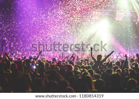 A crowded concert hall with scene stage lights, rock show performance, with people silhouette  #1180854319