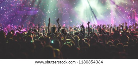 A crowded concert hall with scene stage lights, rock show performance, with people silhouette  #1180854364