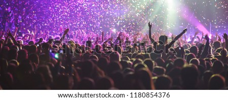 A crowded concert hall with scene stage lights, rock show performance, with people silhouette  #1180854376