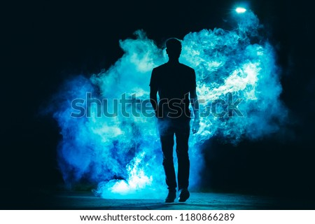 The male walking in the blue smoke on the dark background. evening night time #1180866289