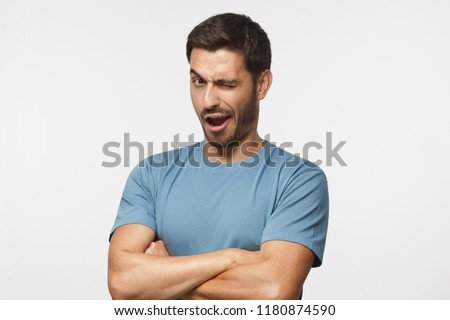 Studio shot of young man winking while flirting, isolated on gray background #1180874590