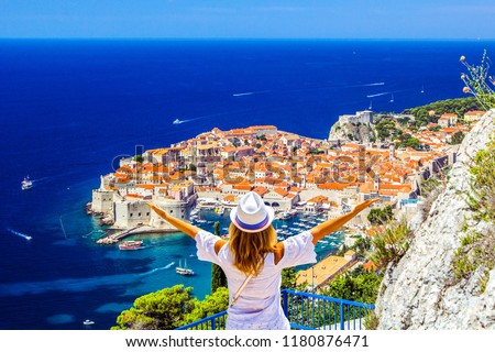 Happy woman enjoys view of old town (medieval Ragusa) and Dalmatian Coast of Adriatic Sea in Dubrovnik. Blue sea with white yachts, beautiful landscape, aerial view, Dubrovnik, Croatia #1180876471
