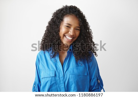Genuine human facial expressions, emotions and feelings. Isolated picture of cheerful relaxed young dark skinned lady with dazzlign ultrawhite smile laughing at joke, posing isolated in studio #1180886197