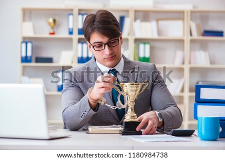 Businessman with golden cup in the office #1180984738