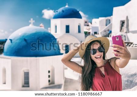 Santorini vacation travel selfie girl taking photo having fun on European cruise holidays. Tourists lifestyle. Smiling Asian chinese tourist woman.