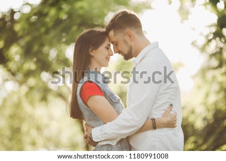 Portrait of young romantic couple in love, smiling and embracing in garden. Sweet lovers in casual clothes, posing touching each other face to face, standing in summer park. Sunset time. #1180991008
