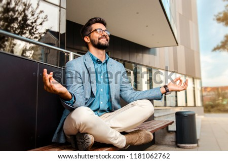Businessman - mentally preparing for business meeting. Sitting in meditation pose in front of office building and smiling   #1181062762