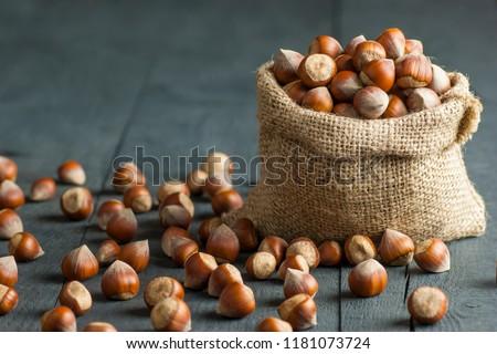 Hazelnuts, filbert in burlap sack on wooden backdrop. heap or stack of hazelnuts. Hazelnut background, healty food #1181073724