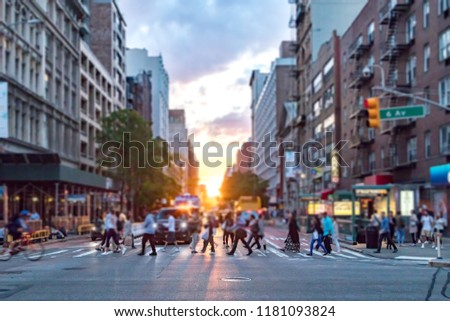 Diverse crowd of people walking across the busy intersection of 23rd Street and 6th Avenue in Manhattan New York City with the colorful light of sunset in the background #1181093824