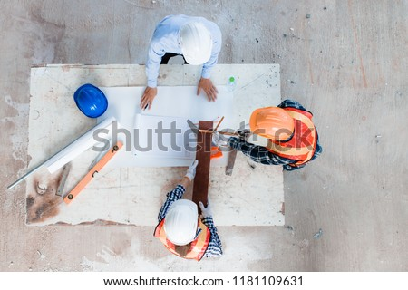 Team of young man and woman engineer and architects working, meeting, discussing, designing, planing, measuring layout of building blueprints in construction site floor at factory. Top view. #1181109631