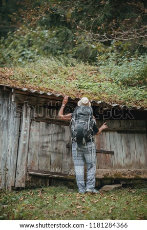 Young traveller examines the old fairytale looking wooden house  #1181284366