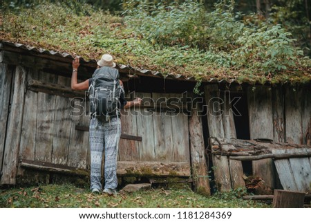 Young traveller examines the old fairytale looking wooden house  #1181284369
