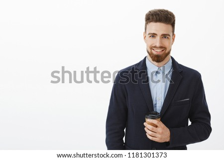 Money likes confidence. Self-assured charismatic and intelligent handsome man with brown hair, beard and blue eyes holding paper cup of coffee smiling happily meeting cute girl after work in cafe #1181301373