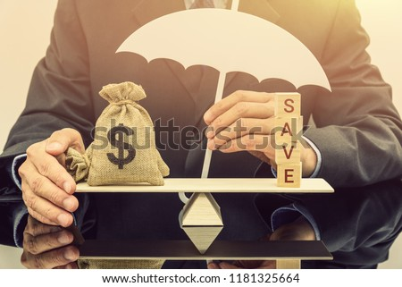 Savings protection / keep money safe concept : Businessman holds a white umbrella protects or guards a dollar money bags on a balance scale, depicts protection when bank or building society goes bust. #1181325664