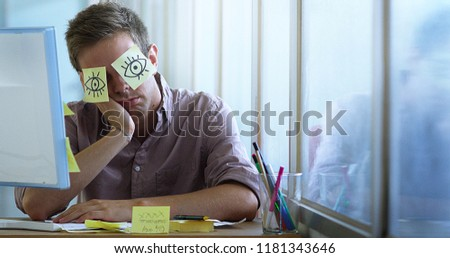 young office worker taking a break,He jokes with a sticky notes stuck in the eyes to sleep #1181343646