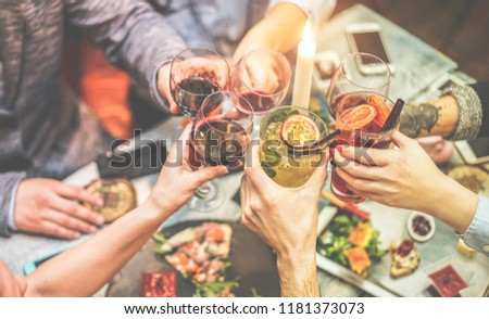 Group of trendy friends enjoying appetizer in american bar - Young people hands cheering with wine and tropical fruits cocktails - Radial purple and green filters editing - Focus on right hand glass #1181373073