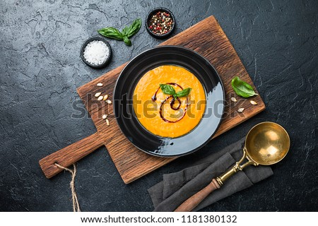 Pumpkin and carrot soup with cream and basil in black plate over dark background Top view Copy space #1181380132