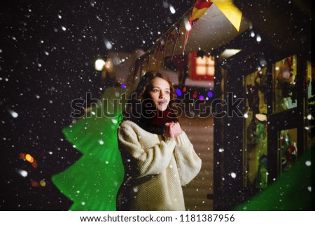 A young girl walks through the evening of the city, among the Christmas decorations. Night photography. The concept of magic and expectations of the holiday. #1181387956