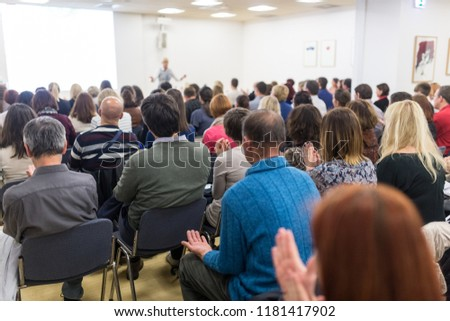 Life coaching symposium. Female speaker giving interactive motivational speech at entrepreneurship workshop. Audience in conference hall. Rear view of unrecognized participant. #1181417902