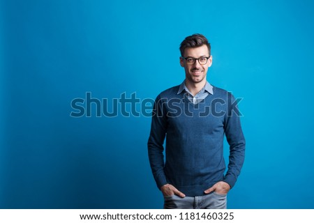 Portrait of a young man with glasses in a studio on a blue background. #1181460325