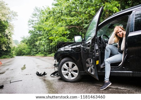 Young woman in the damaged car after a car accident, making a phone call. #1181463460