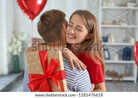 Young couple with gift box hugging at home #1181476618
