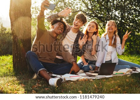 Group of cheerful multhiethnic students doing homework together at the park, using laptop computer, taking a selfie with mobile phone #1181479240