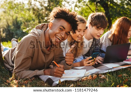 Group of laughing multhiethnic students doing homework together at the park, using laptop computer and mobile phone, laying on a grass #1181479246