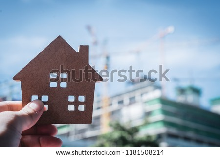 House model in home insurance broker agent 's hand or in salesman person with blur building. Real estate agent offer house, property insurance and security, affordable housing concepts #1181508214