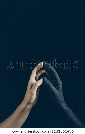 cropped view of woman touching with black demon hand isolated on black #1181551495