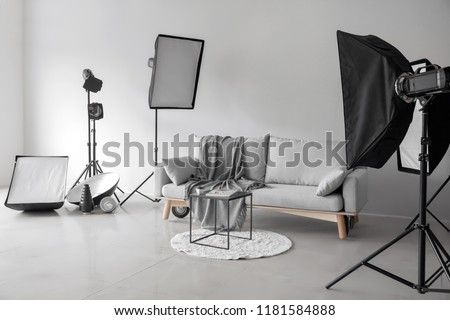 Cozy sofa and table in photo studio with professional equipment