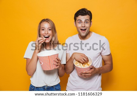 Happy young couple standing isolated over background, eating popcorn #1181606329