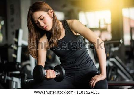 Fitness woman in training exercises with dumbbells. #1181624137