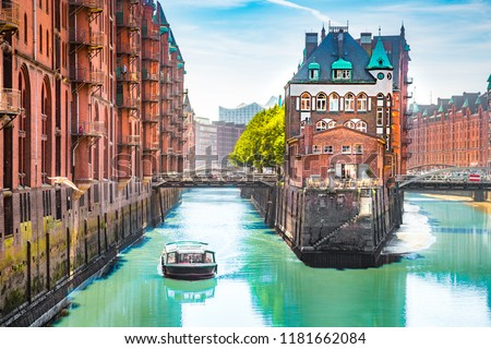 Classic view of famous Hamburg Speicherstadt warehouse district with sightseeing tour boat on a sunny day in summer, Hamburg, Germany #1181662084