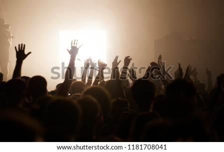 Crowd at concert - Cheering crowd in bright colorful stage lights #1181708041