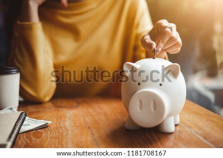 woman hand putting money coin into piggy for saving money wealth and financial concept. #1181708167