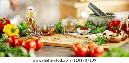 Panorama banner with fresh culinary herbs and spices on a chopping board with a pestle and mortar surrounded by fresh vegetables for salads #1181787109