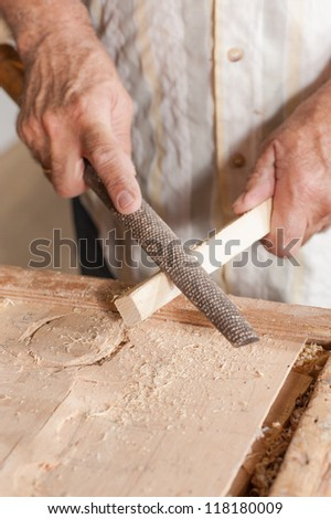 Carpenter working with a traditional rasp tool #118180009