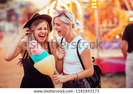 Happy female friends in amusement park eating cotton candy. Two young women enjoying a day at amusement park. Royalty-Free Stock Photo #1181843173