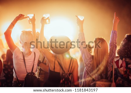 Back view of group of female friends at music festival drinking beer and dancing #1181843197