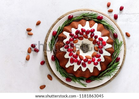 Christmas festive pound cake decorated with cranberries almonds and rosemary twigs, view from above #1181863045