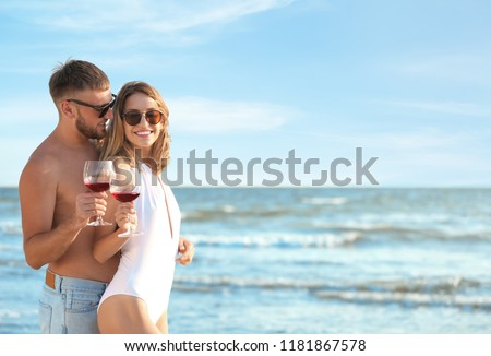 Young couple with glasses of wine on beach #1181867578
