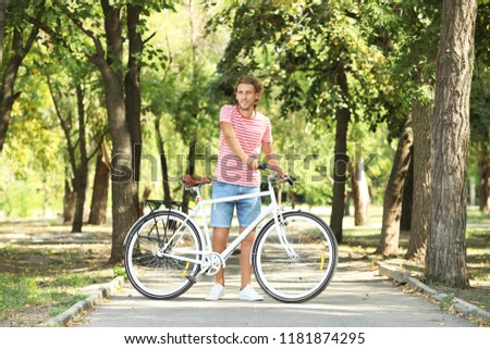 Handsome man with bicycle in park on sunny day #1181874295